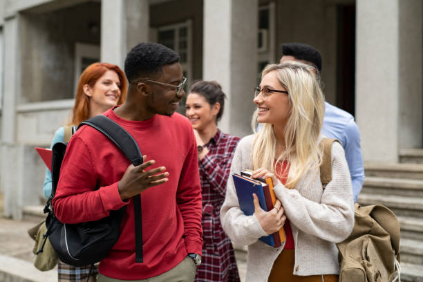 Multiethnic student friends walking in college campus stock photo