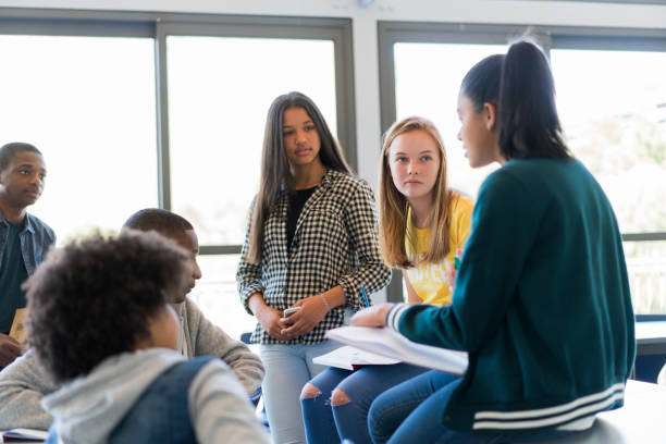 multi-ethnic students discussing in classroom - ragazzi adolescenti foto e immagini stock