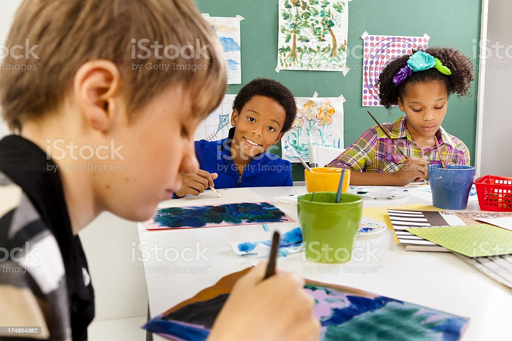 Multi-ethnic students in art class. Painting with watercolors royalty-free stock photo