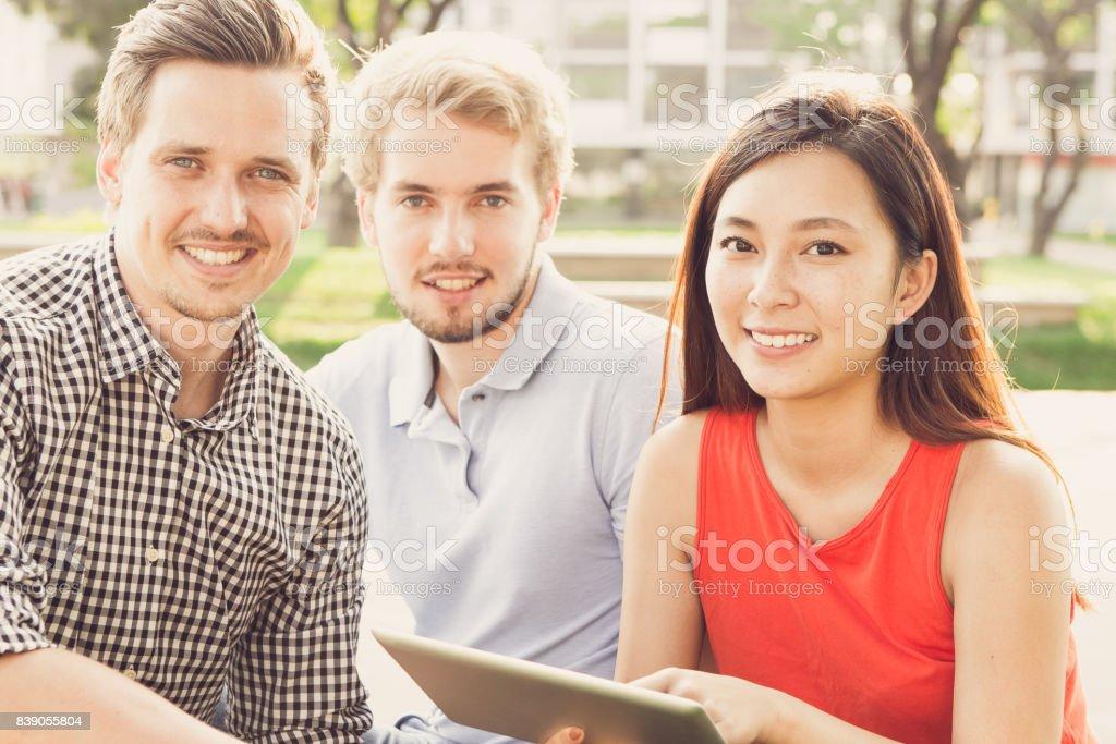 Multi-ethnic students resting in park stock photo