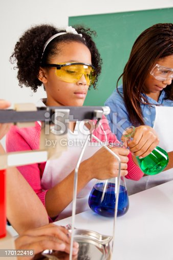 istock Multi-Ethnic students science lab safety glasses using scale and beaker 170122416