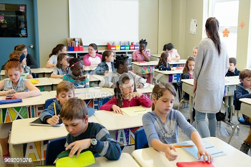 Multi-ethnic schoolgirls and shcoolboys sit into the class for their first day at school. Some of them are shy and other expressive.  There is multicolour name in the front of the desk. Photo was taken in Quebec Canada.