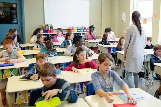 multi-ethnic students sit into the class for the first day at school - manonallard stock photos and pictures