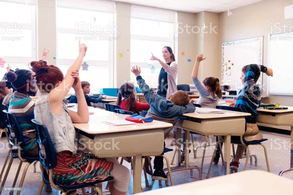 Multi-ethnic schoolgirls and shcoolboys sit into the class with arms...