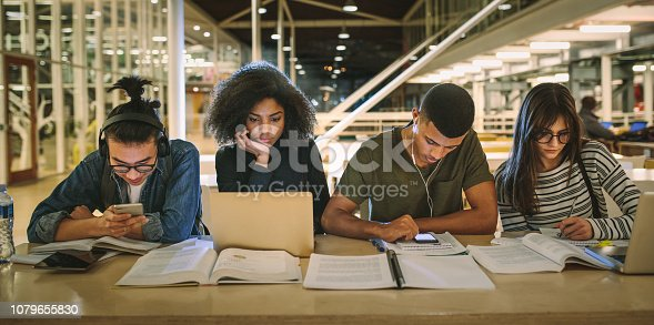 Multi-ethnic students sitting at college library. Students using making notes, using laptop and mobile phones while studying together.