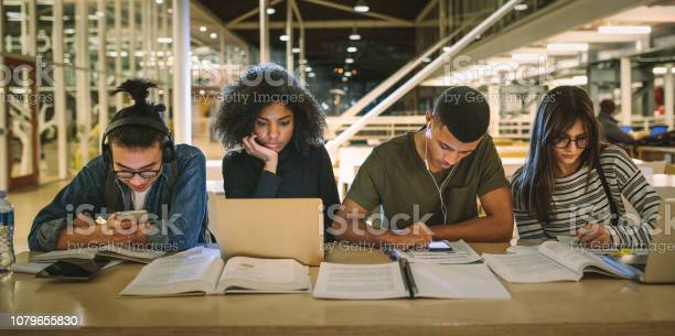 Multi-ethnic students sitting at college library Multi-ethnic students sitting at college library. Students using making notes, using laptop and mobile phones while studying together. Adult Stock Photo