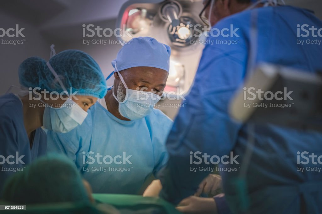 Multi-ethnic surgeons performing surgery on patient in operating...