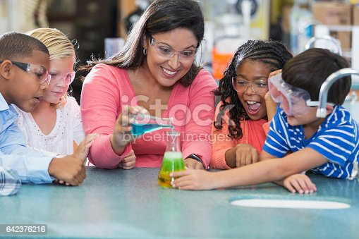An Hispanic woman in her 40s teaching a multi-ethnic group of elementary school students in science lab. They are doing an chemistry experiment with colorful liquids in beakers.