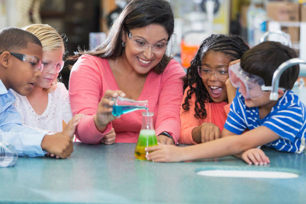 Multi-ethnic teacher and children in science lab An Hispanic woman in her 40s teaching a multi-ethnic group of elementary school students in science lab. They are doing an chemistry experiment with colorful liquids in beakers. elementary age stock pictures, royalty-free photos & images
