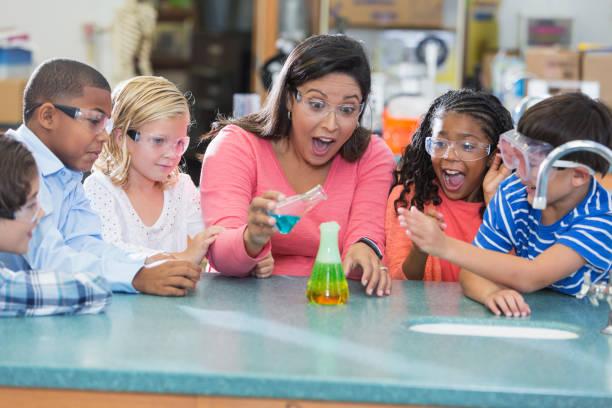 professor multi-étnica e crianças no laboratório de ciências - aula de ciências - fotografias e filmes do acervo
