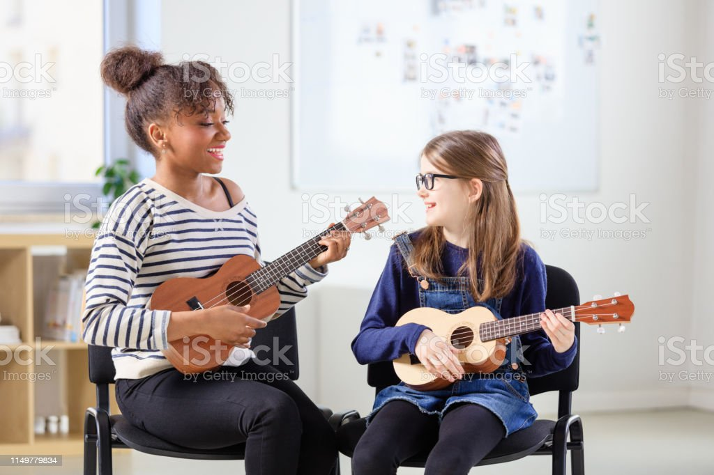 Multi-ethnic teacher and student playing ukulele Smiling multi-ethnic females playing ukulele in class. Instructor teaching music to pre-adolescent student. They are sitting in classroom at education building. 10-11 Years Stock Photo