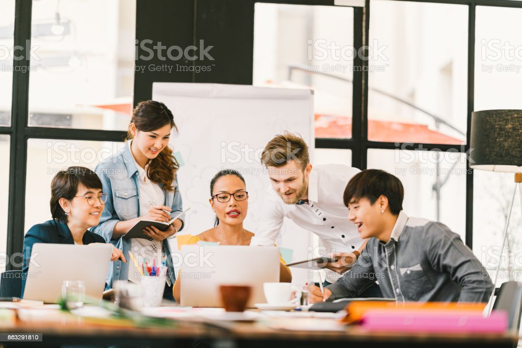 Multiethnic team busy discussion using laptop, digital tablet. Coworker partnership, college student meeting. Small business casual office, freelance designer job, or online marketing analysis concept royalty-free stock photo