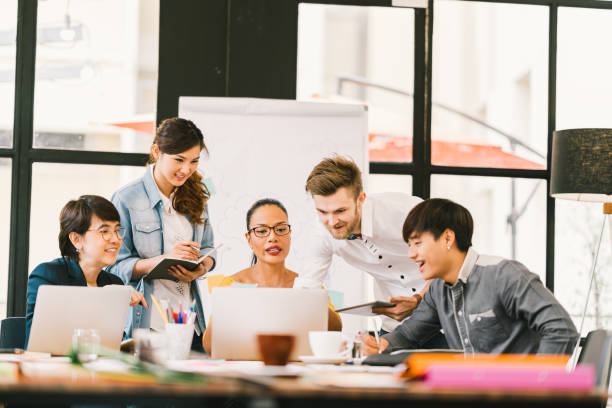 multiethnic team busy discussion using laptop, digital tablet. coworker partnership, college student meeting. small business casual office, freelance designer job, or online marketing analysis concept - digital marketing stock photos and pictures