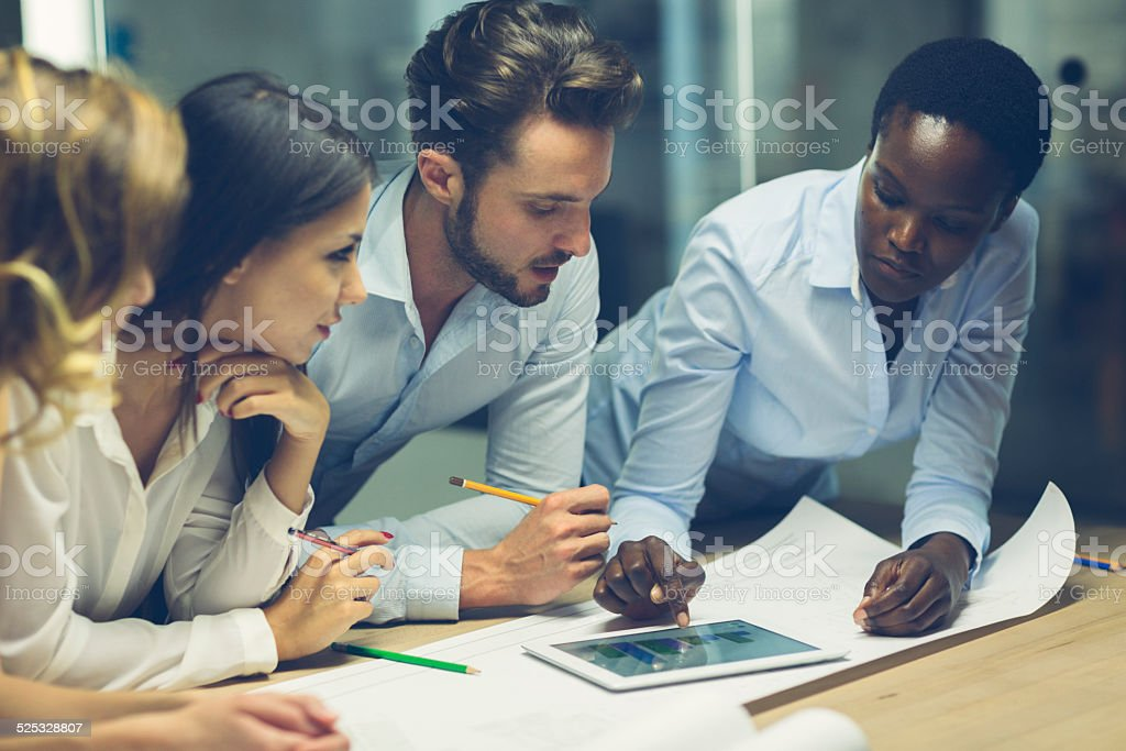 Multiethnic Team of architects reviewing reports in the office. stock photo
