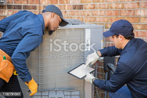 Multi-ethnic team of blue collar air conditioner repairmen at work.  They prepare to begin work by gathering appropriate tools from their tool box.
