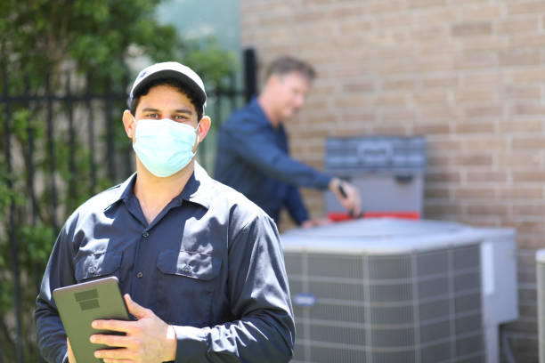 Multi-ethnic team of blue collar air conditioner repairmen at work. Multi-ethnic, mixed age team of blue collar air conditioner repairmen working at residential home.  They prepare to begin work by gathering appropriate tools and referring to digital tablet. Latin descent man stands out front wearing mask. covid-19 stock pictures, royalty-free photos & images