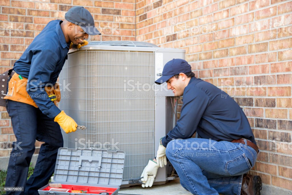 Multi-ethnic team of blue collar air conditioner repairmen at work. stock photo