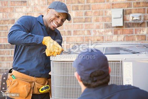 istock Multi-ethnic team of blue collar air conditioner repairmen at work. 944678614