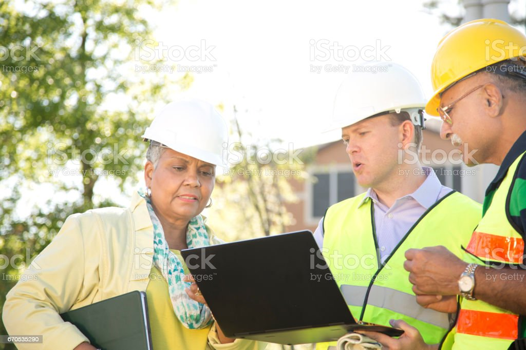 Multi-ethnic team of construction engineer, architect and worker at job site. stock photo