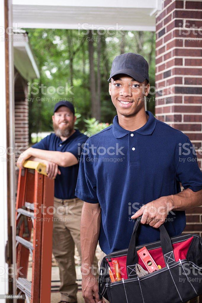 Multi-ethnic team of repairmen at customer's front door. stock photo