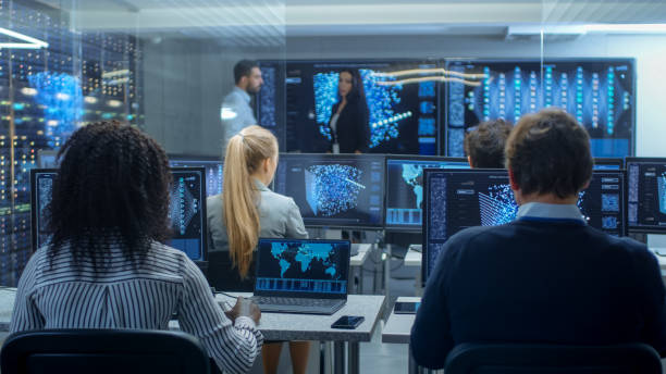 Multi-Ethnic Team of Research Engineers, Neural Network Architects, Programmists Working on a Machine Learning, Neural Network Building Project. Office Displays Show Working Model of Neural Network. stock photo