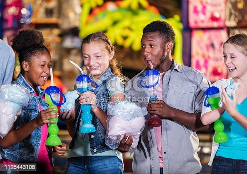 istock Multi-ethnic teenage friends in amusement arcade eating 1125443108