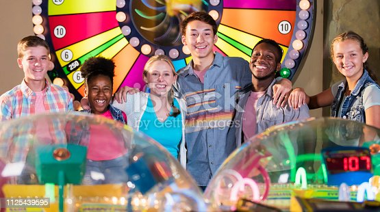 istock Multi-ethnic teenage friends in amusement arcade 1125439595