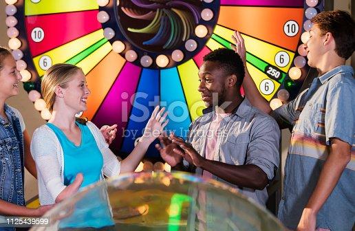 istock Multi-ethnic teenage friends in amusement arcade 1125439599