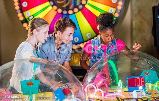 istock Multi-ethnic teenage friends playing arcade games 1125439877
