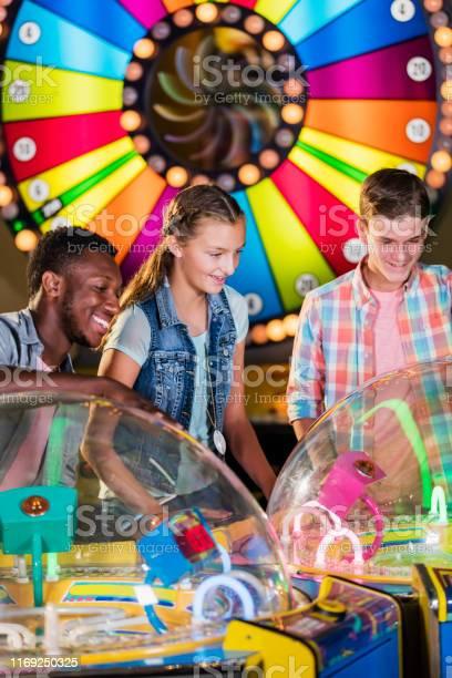 Multiethnic teenage friends playing arcade games picture id1169250325?b=1&k=6&m=1169250325&s=612x612&h=tzluobhk0womcb1ak09glowry71qnwxwdshb vjexlq=