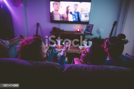 Young multi-ethnic hipster friends relaxing on living room sofa and watching film on TV
