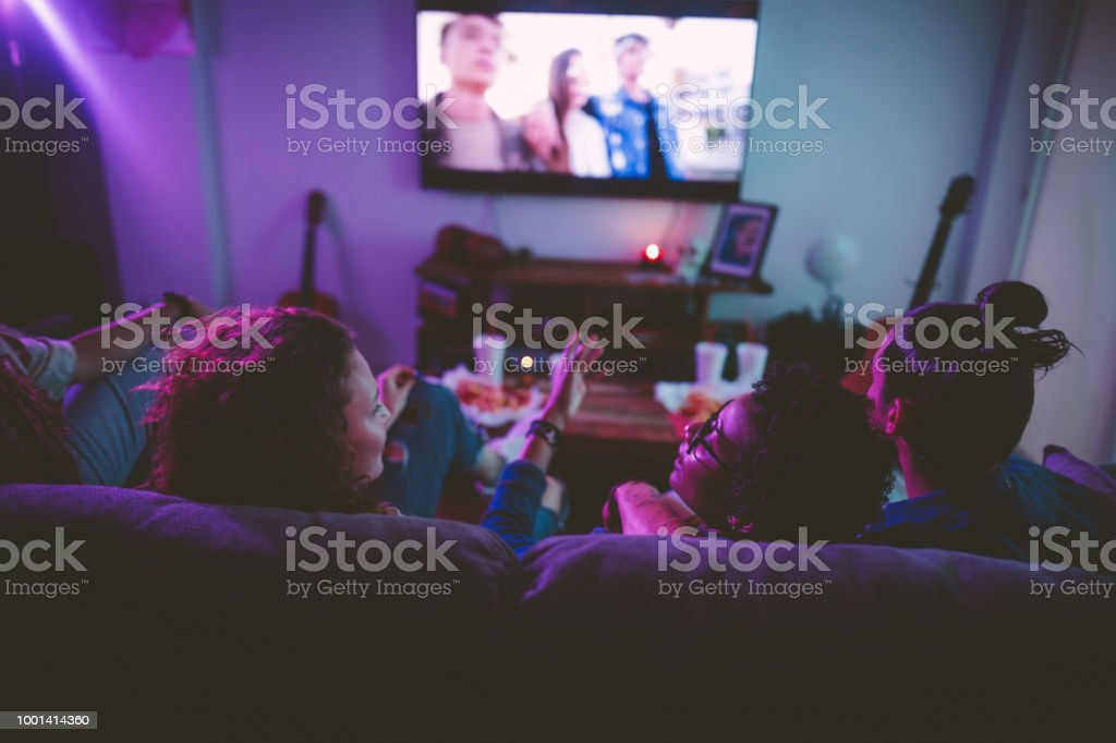 Multi-ethnic teenage friends watching TV together at hangout house stock photo