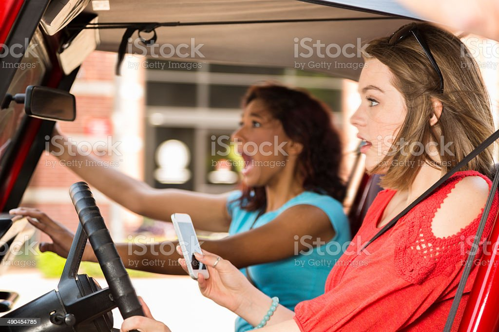Multi-ethnic teenage girls texting while driving their car. Crash! Texting and driving. Two distracted, multi-ethnic teen girls text message on smart phone while driving vehicle. They are about to crash as a result of texting and driving.   16-17 Years Stock Photo