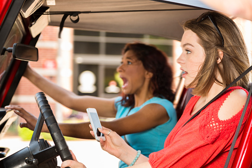 Multiethnic Teenage Girls Texting While Driving Their Car Crash Stock Photo - Download Image Now