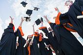 Multi-ethnic teenage graduates throw caps in air