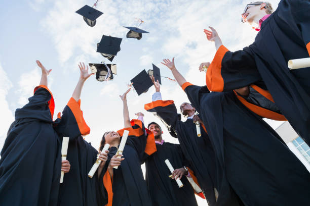 Multi-ethnic teenage graduates throw caps in air stock photo