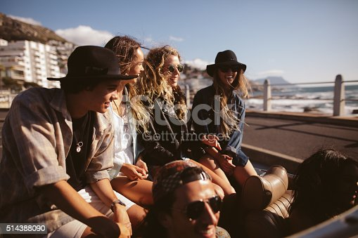 Group of multi-ethnic teenager friends wearing hipster outfits sitting in a convertible for a summer road trip