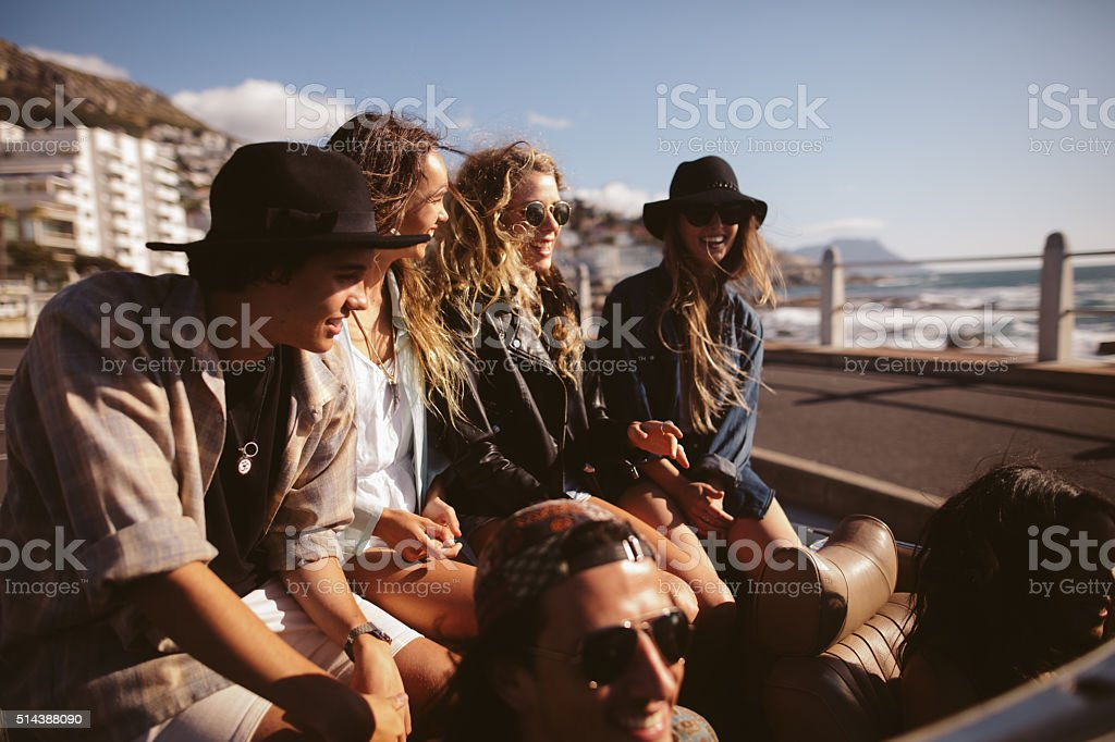 Multi-ethnic teenager friends on a summer road trip with convertible stock photo