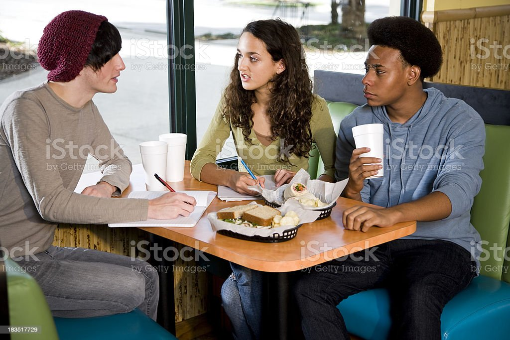 Multi-ethnic teenagers studying in restaurant over lunch stock photo