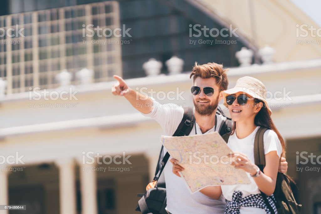 Multiethnic traveler couple using generic local map together on sunny day, man pointing toward copy space. Honeymoon trip, backpacker tourist, Asia tourism, or holiday vacation travel concept - Photo