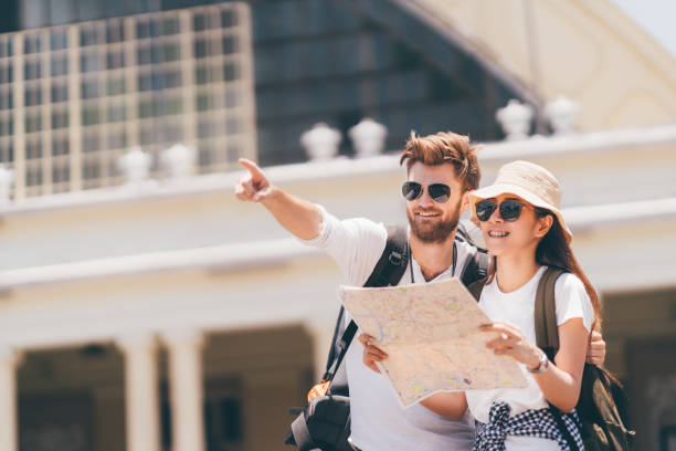 Multiethnic traveler couple using generic local map together on sunny day, man pointing toward copy space. Honeymoon trip, backpacker tourist, Asia tourism, or holiday vacation travel concept - foto stock