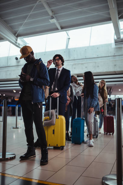 Multi-ethnic travelers waiting in line for check-in at airport stock photo