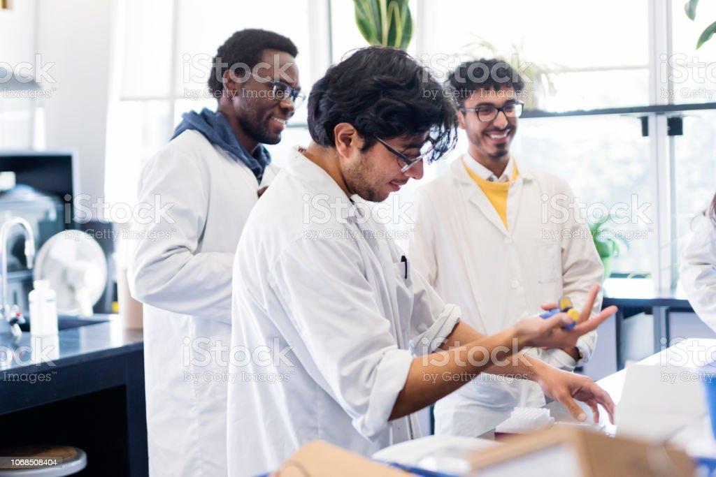 Multi-ethnic trio of professors and student in college science laboratory. stock photo
