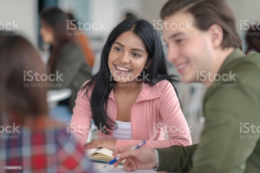 A multi-ethnic group of students sits at a table while communicating...