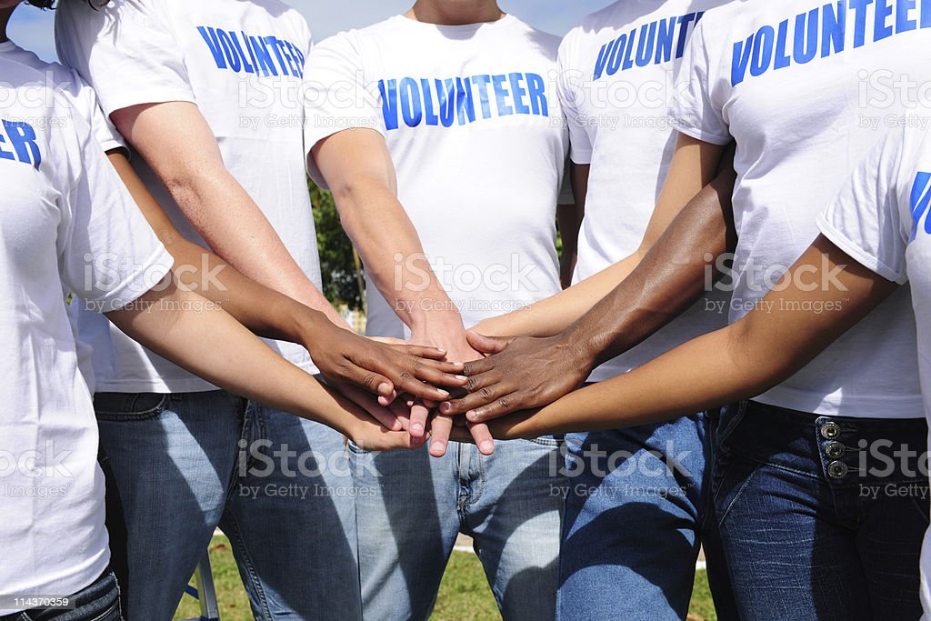 multi-ethnic volunteer group hands together stock photo
