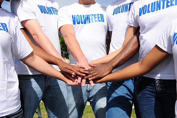 multi-ethnic volunteer group hands together - volunteer stock photos and pictures
