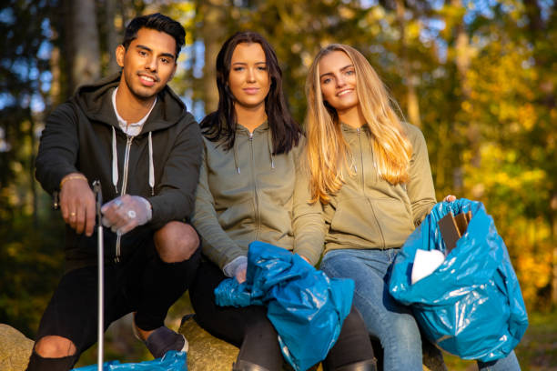 Multi-ethnic volunteers in environmental protection team sitting with garbage bags stock photo