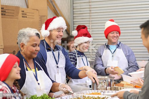 Multi-ethnic, mixed age group of volunteers serves food at a soup kitchen.  A variety of food is being served to the under-resourced people in their local community.  Christmas season.