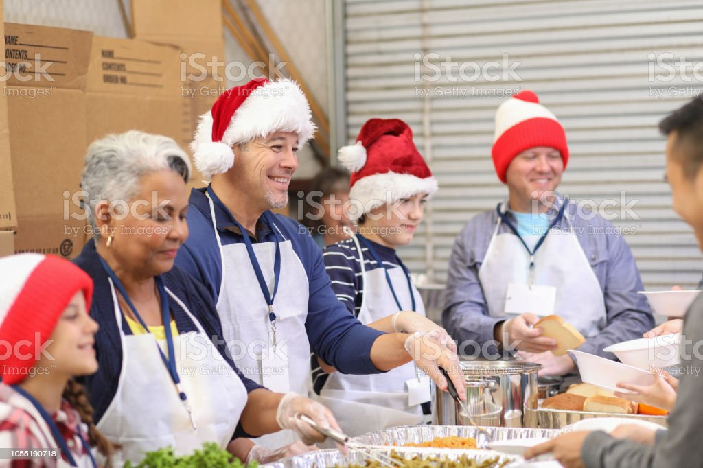Multi-ethnic volunteers serves food at soup kitchen at Christmas. stock photo