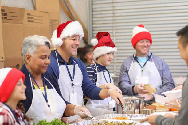 multi-ethnic volunteers serves food at soup kitchen at christmas. - fondazione di beneficienza foto e immagini stock